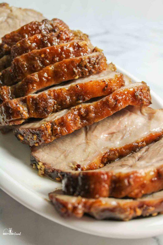 juicy sliced pork roast on a cutting iard