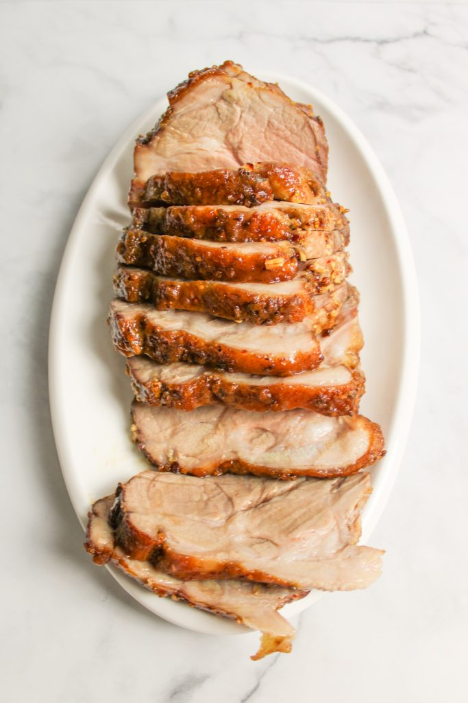 a cooked pork roast cut open on a cutting board