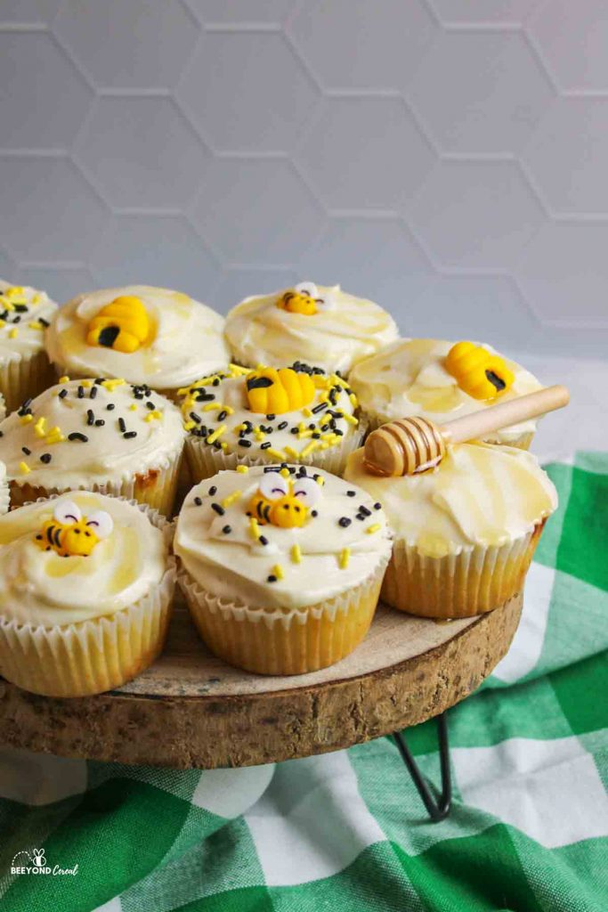 honey cupcakes with bees and hives and sprinkles on a wooden cake stand