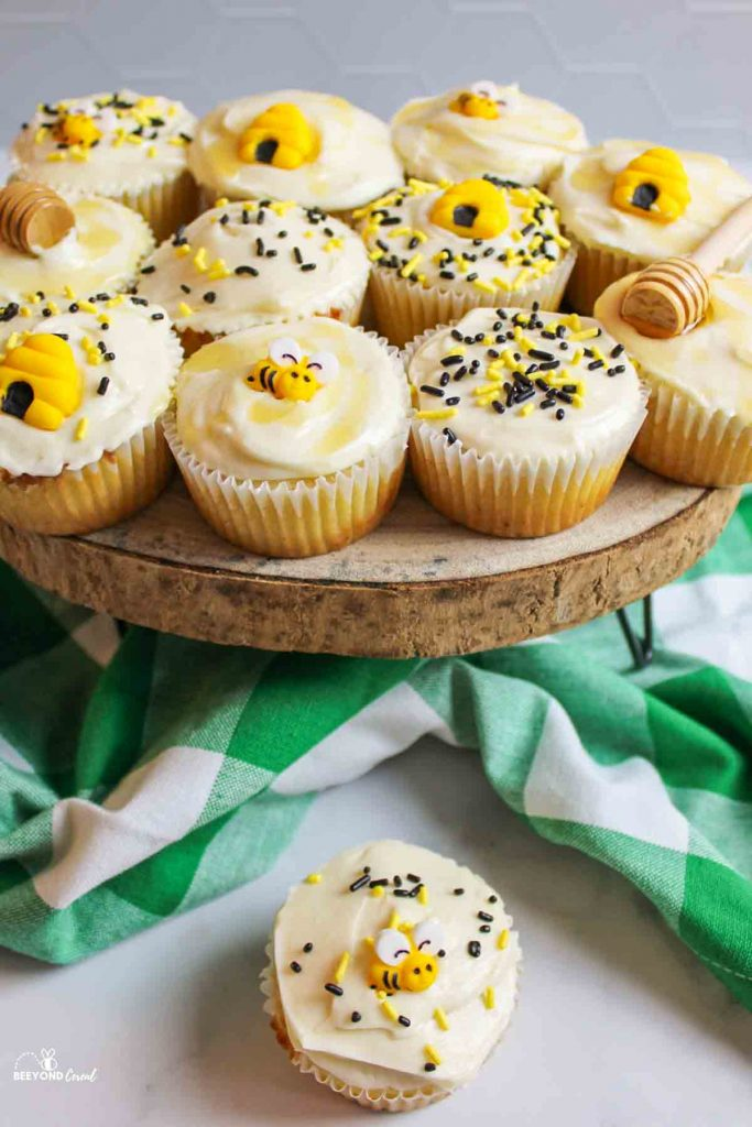a decorated honey bee cupcakes below a platter with more cupcakes on top