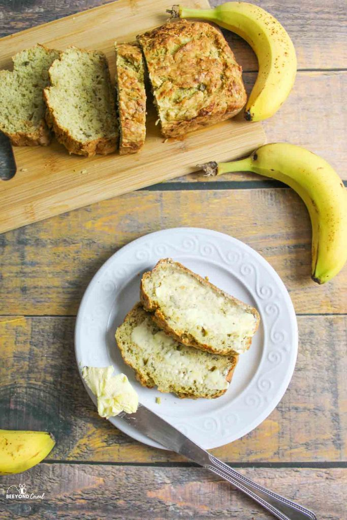 sliced banana bread on a cutting board and two warm slices with vegan butter spread on top