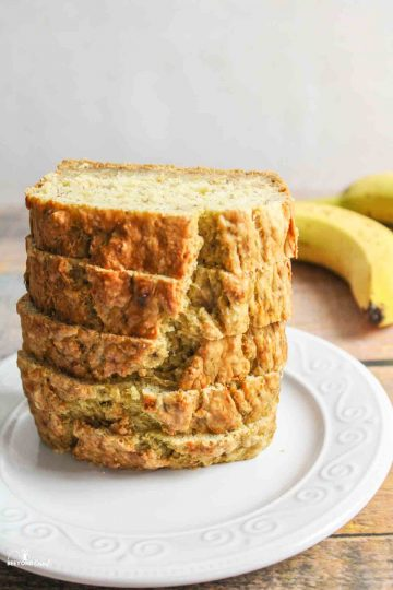 vegan banana bread sliced and stacked several pieces tall on a white plate