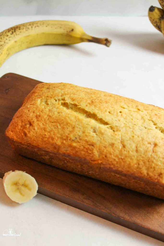 banana bread loaf on cutting board with fresh bananas and slice around it