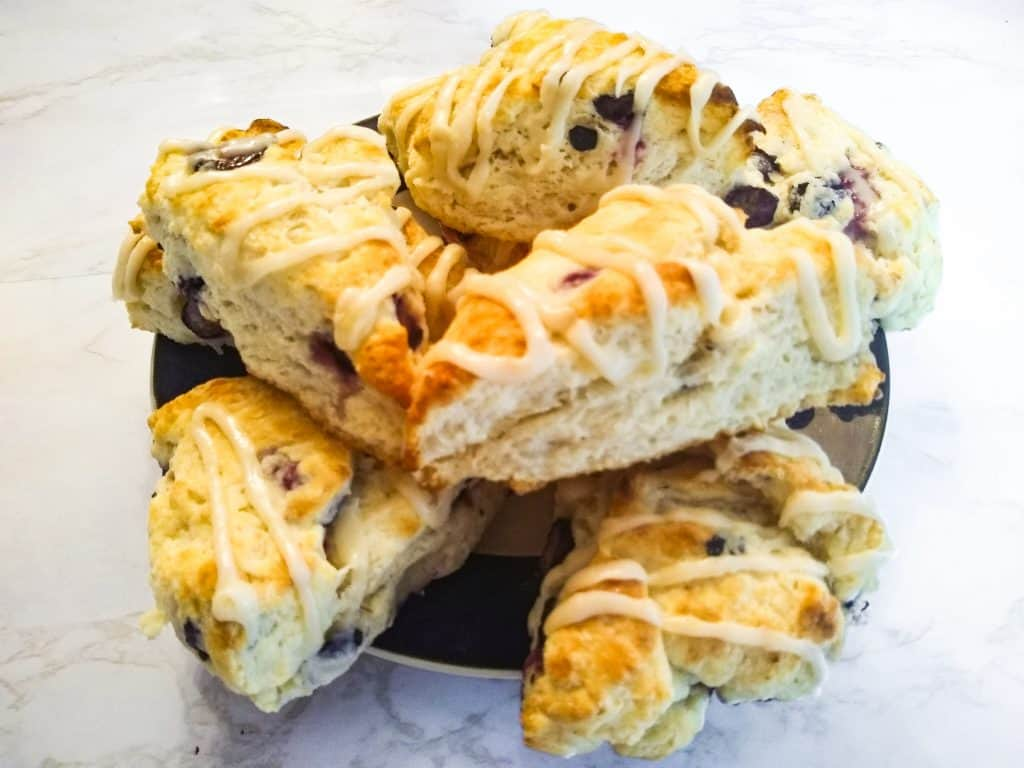 a plate full of glazed blueberry scones