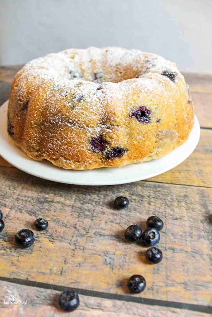A full bundt cake with scattered blueberries in front