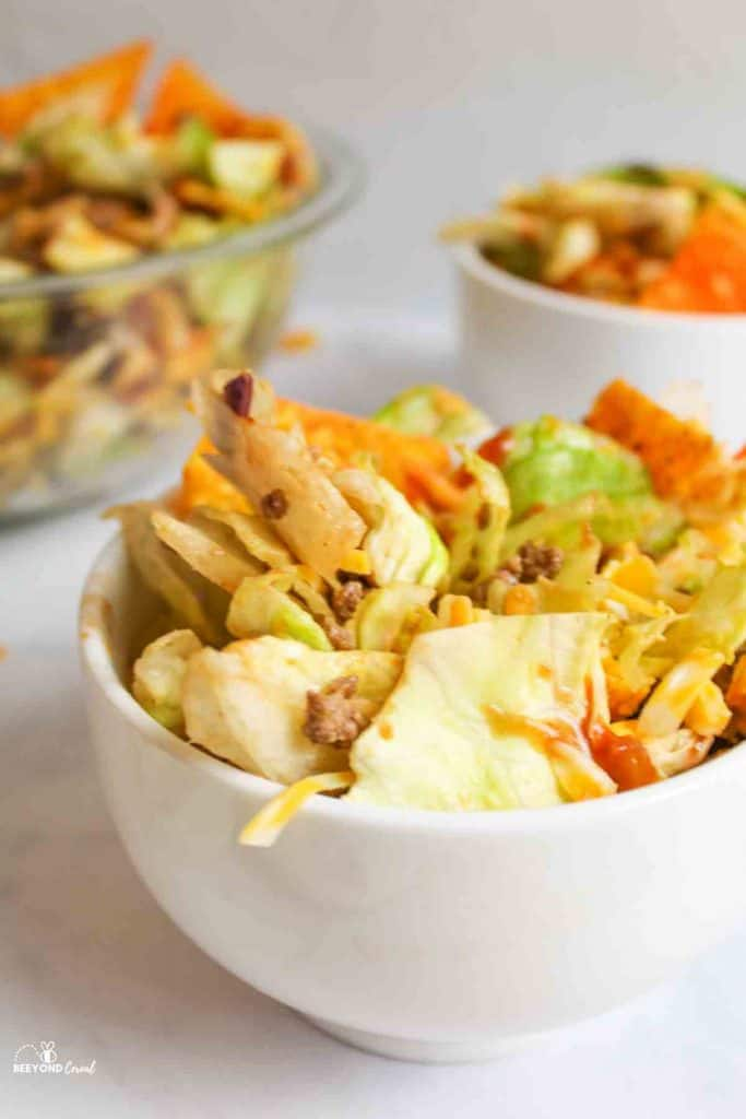 an upclose shot of a serving bowl filled with dorito taco salad and more in bowls in background
