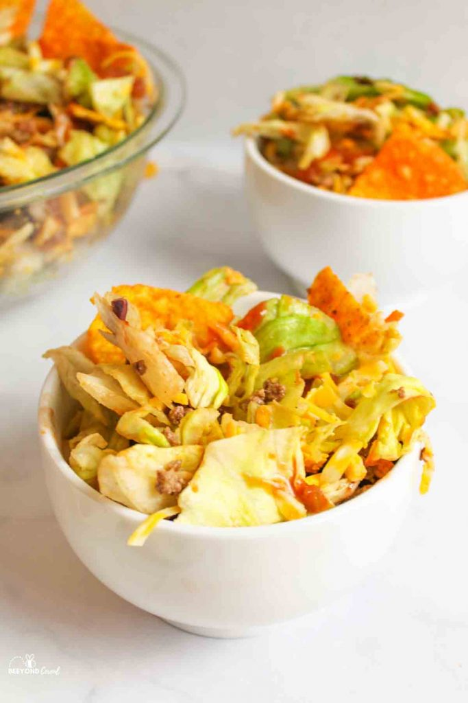 two white bowls ad a glass mixing bowl filled with dorito salad