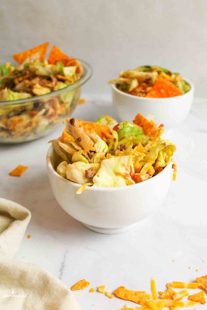 two serving bowls of dorito salad and a mixing bowl filled to the side