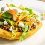 a frybread covered in lettuce meat cheese tomatoes and onion