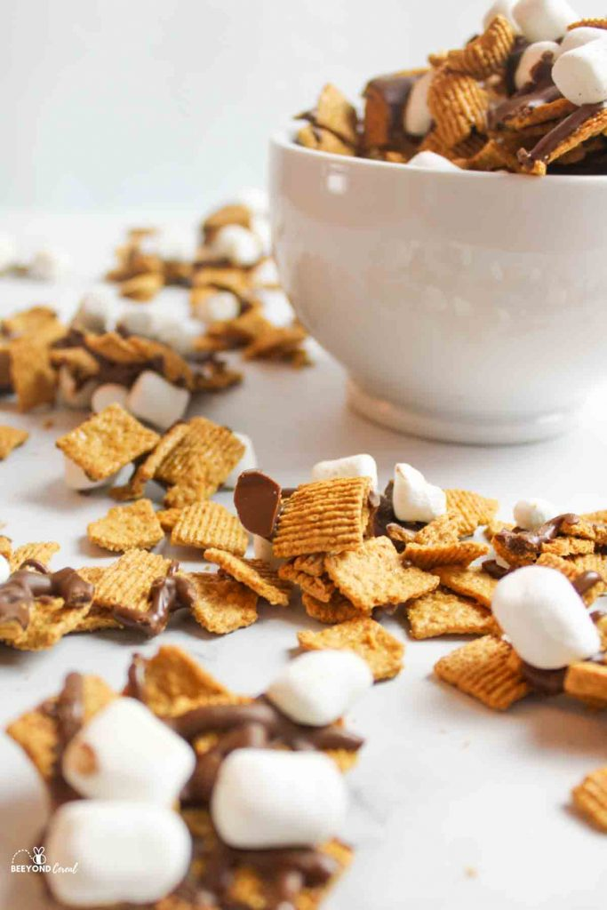 scattered golden grahams mix around a white bowl full of smores mix