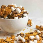 smores snack mix in a white bowl with more scattered around it