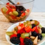 a servng of honey lime fruit salad in a white bowl with mixed fruit behind it