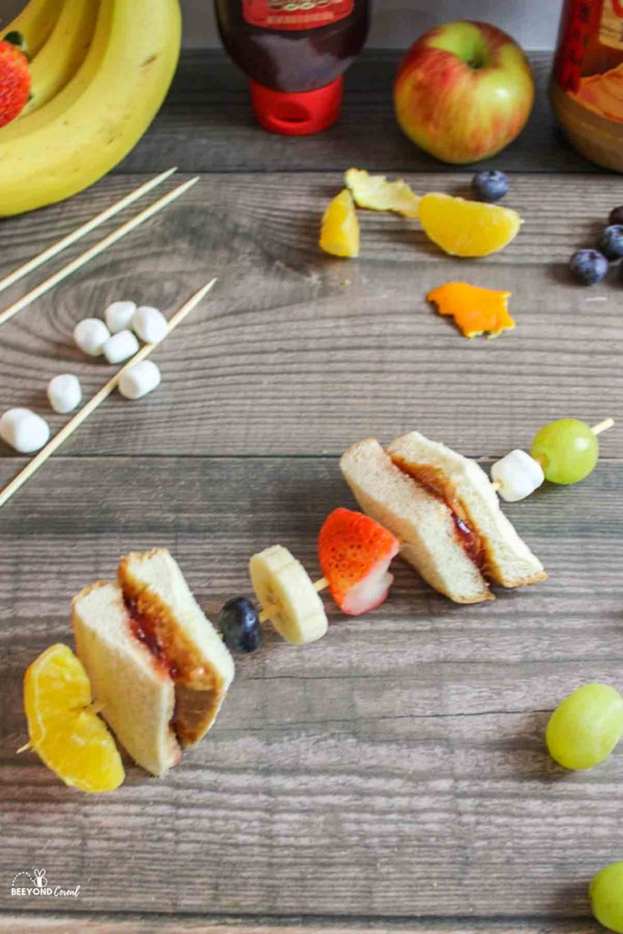 an assembled pbj skewer with fruits around it