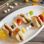 two pbj skewers on a white platter with fresh fruit and ingredients around it