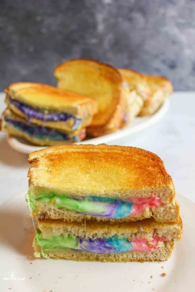 rainbow grilled cheese sandwiches cut to reveal gooey colored cheese inside
