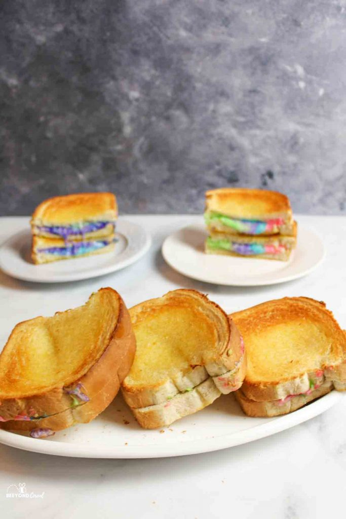 rainbow grilled cheese sandwiches on plates some whole and some sliced in background