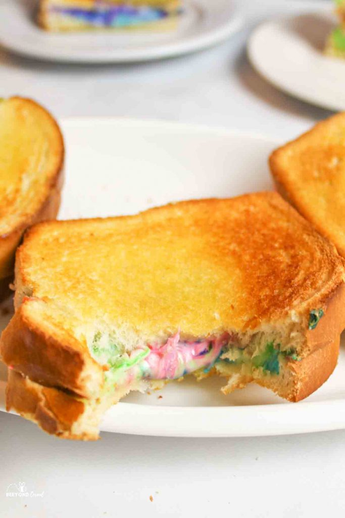 rainbow grilled cheese sandwich with a bite missing