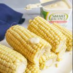 Smart balance and a used butter knife next to buttered corn on the cob