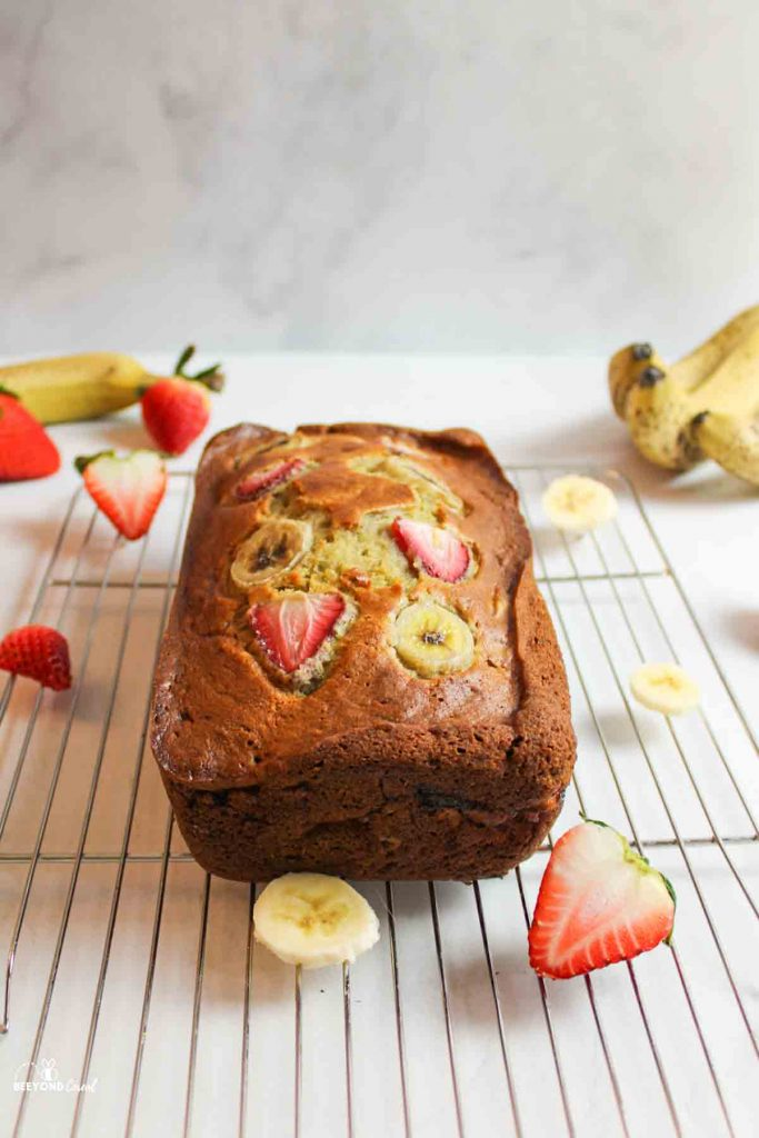 strawberry banana bread on a wire cooling rack with fresh fruits around it