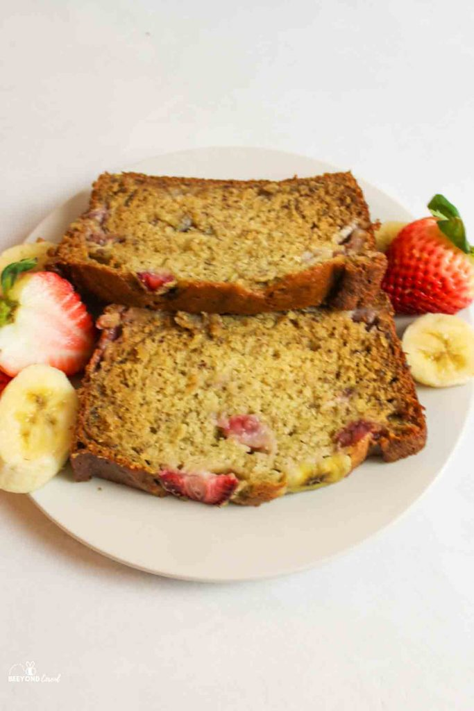 two slices of banana bread with strawberries on a white plate