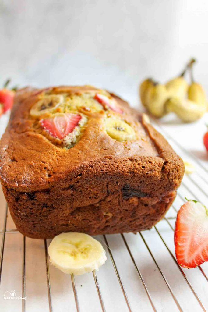 an upclose side view of a loaf of strawberry banana bread on a wire cooling rack