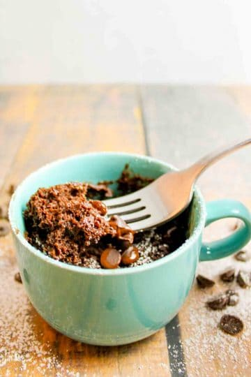 a fork scooping into a mug full of vegan brownie