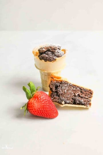 a full brownie cone with a split brownie cone and a fresh strawberry to the front