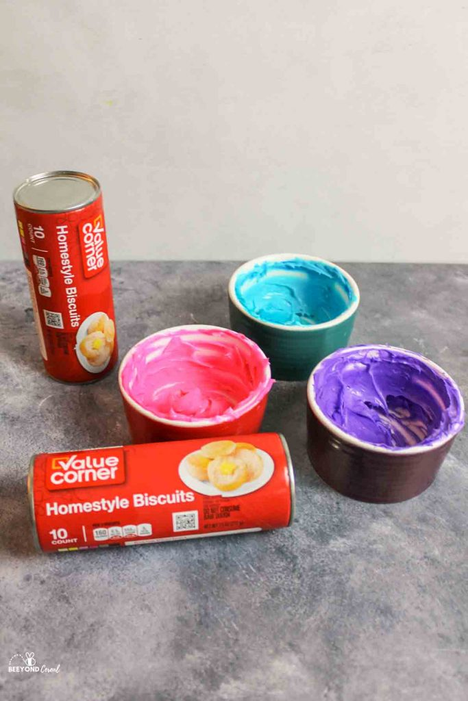 colored cream cheese in containers with two cans of cheap biscuits