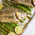 cooked whole fish on asparagus with lemon slices on foil lined baking sheet