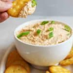a hand holding up a cracker with trout dip on it