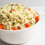 a close side view of a bowl of wild rice pilaf with celery leaves onion and carrots in back