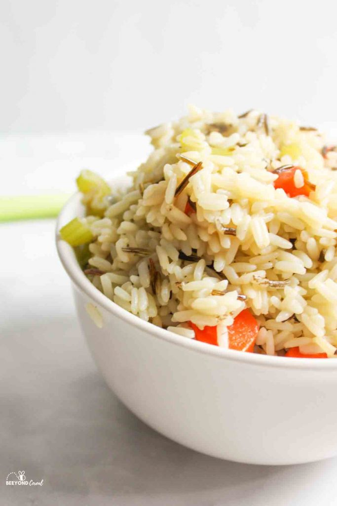 side angle view of a bowl of wild rice pilaf with 2 large carrots celery leaves and an onion in back