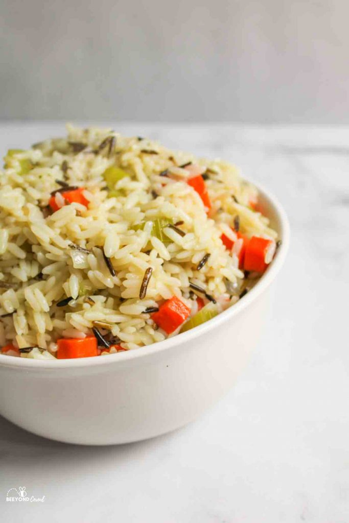 a bowl of wild rice pilaf wth 3 large carrots an onion and some celery