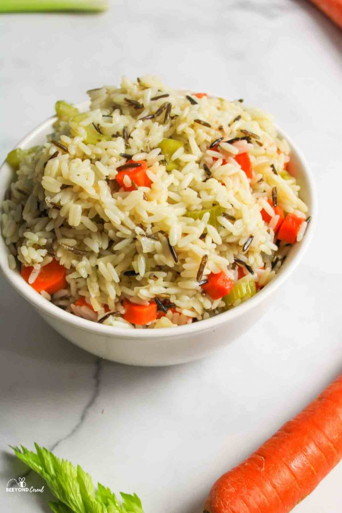 a bowl of wild rice pilaf with large carrots celery top and onion in the picture