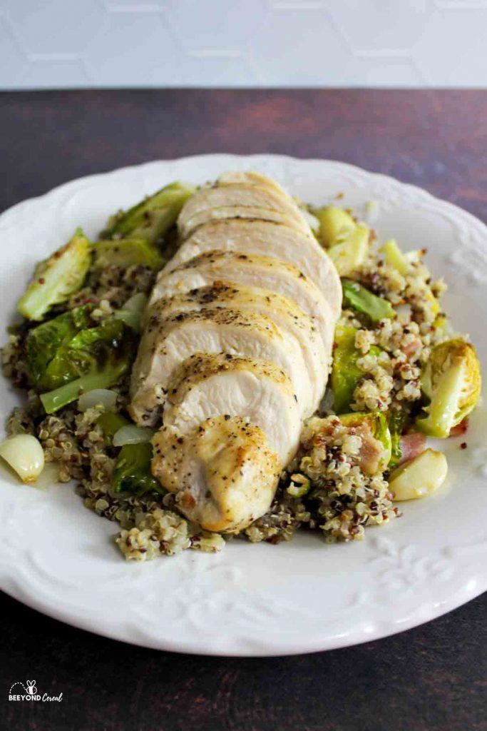 a plate filled with quinoa and brussel sprouts with a sliced chicken breast on top
