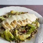 a fork next to a pile of quinoa with brussel sprouts and a sliced chicken breast topped with cheese sauce