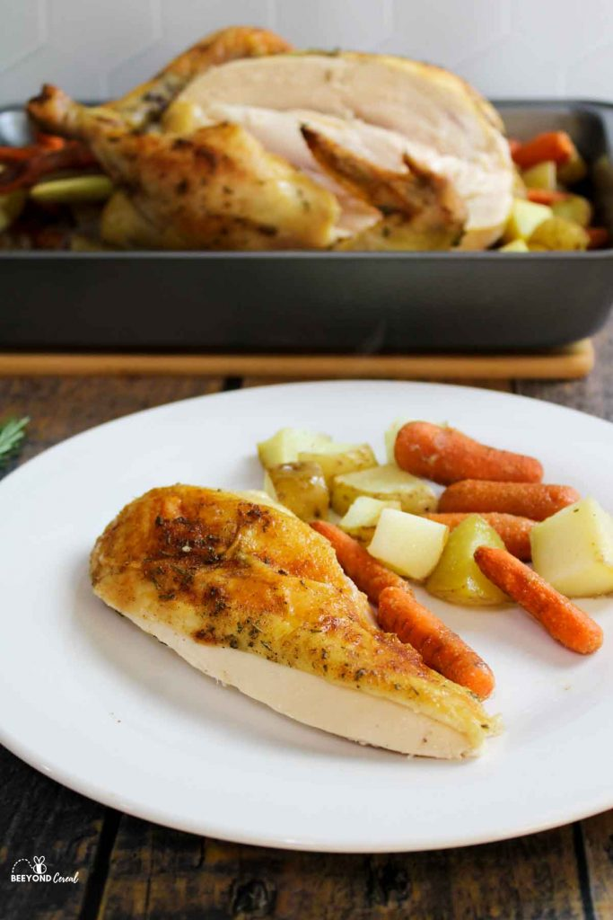 a slice of chicken breast on a white plate with carrots and potatoes