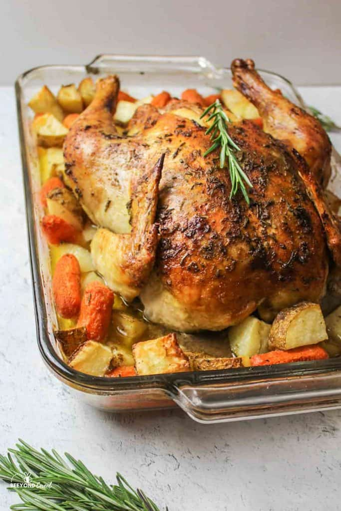baked chicken in a dish with potatoes and carrots