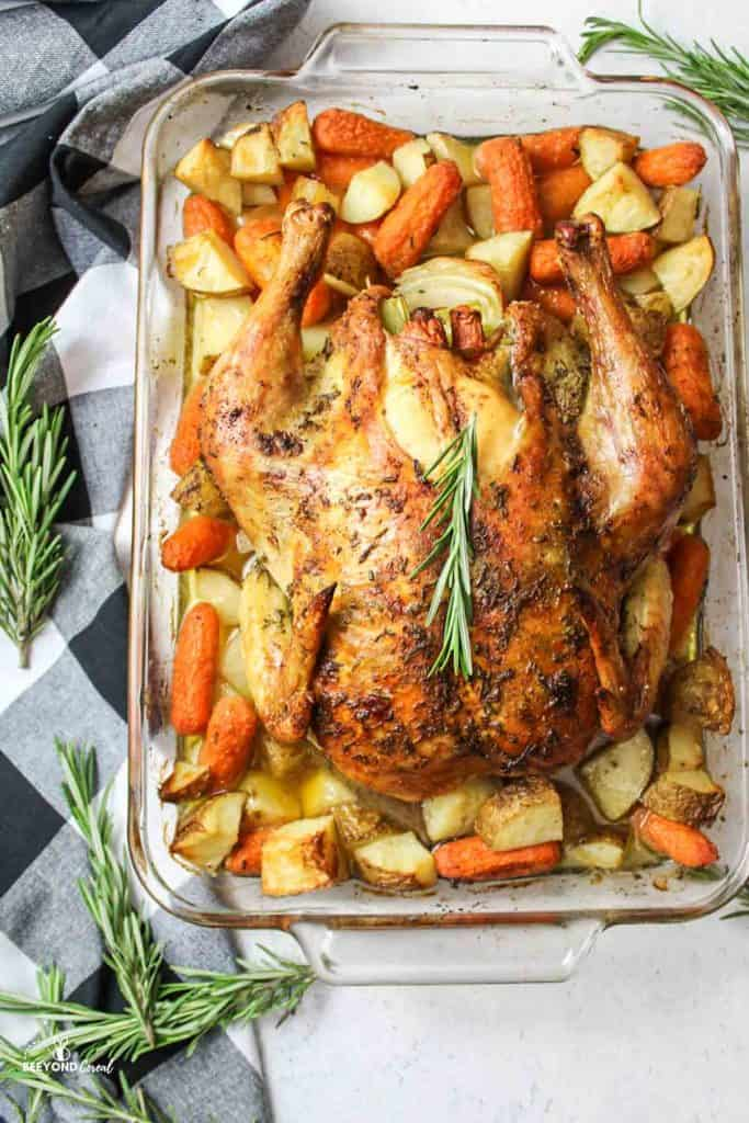 sliced roasted chicken in a baking dish with potatoes and carrots