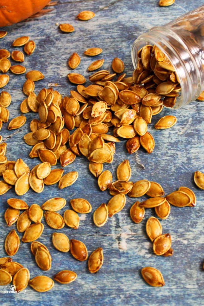 a glass jar tipped over and spilling out honey roasted pumpkin seeds