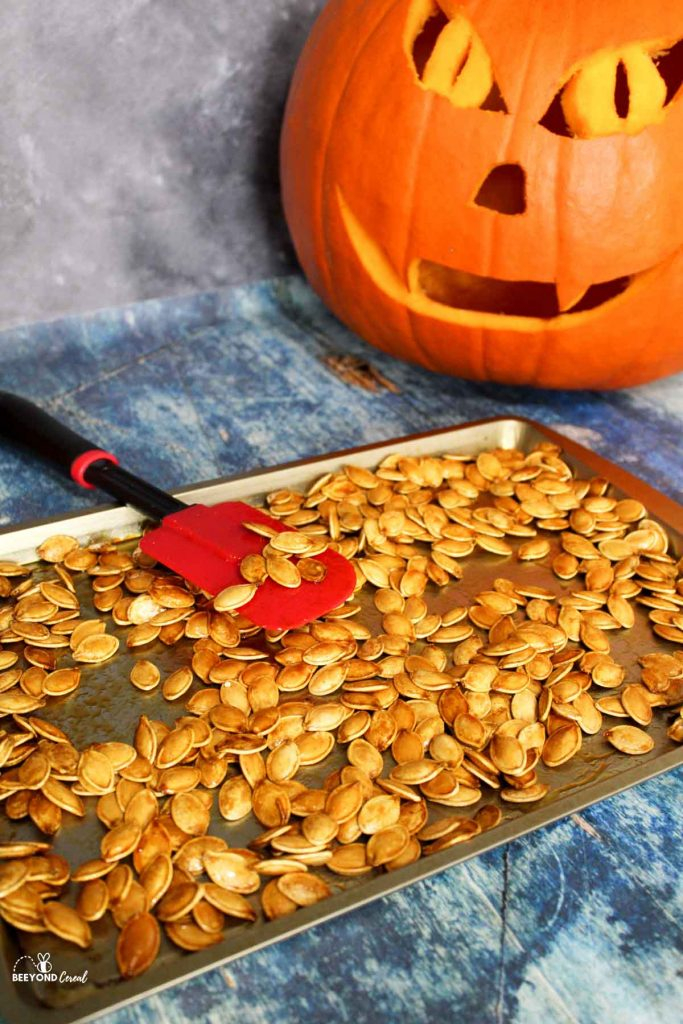 honey roasted pumpkin seeds on a baking sheet with a jack o lantern to the side