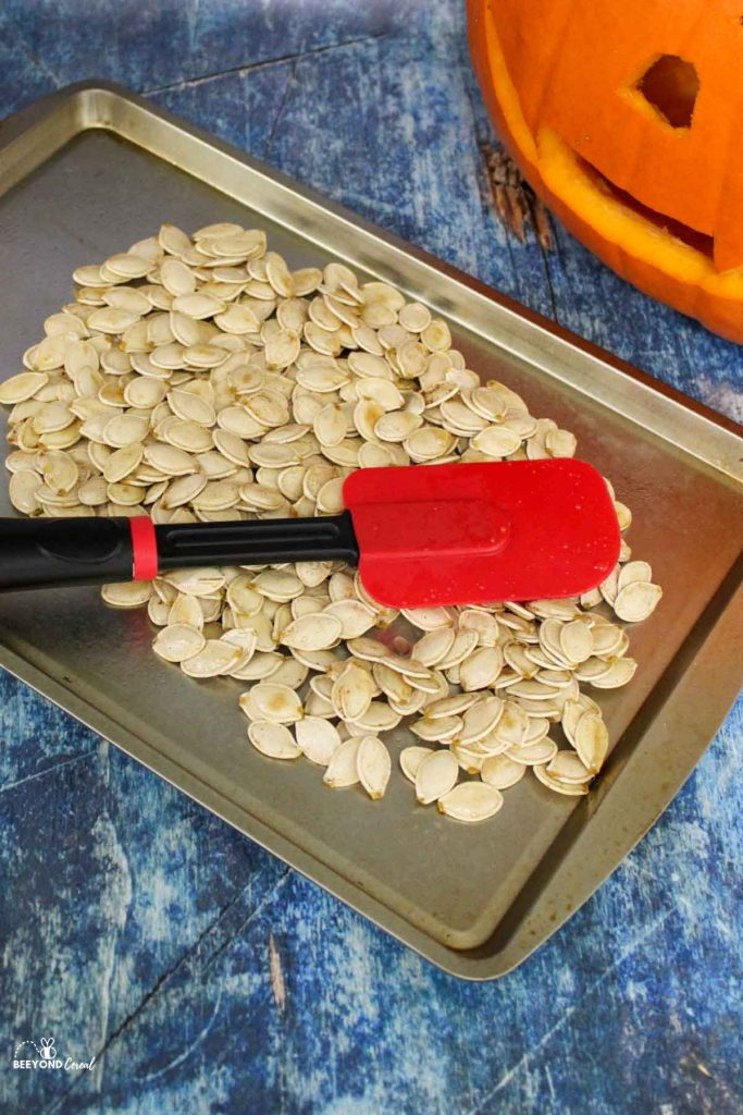 pumpkin seeds being spread out on a baking sheet