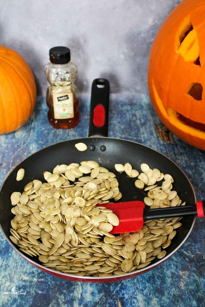 a skillet filled with honey and cinnamon tossed pumpkin seeds