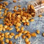 a spilled jar of honey roasted pumpkin seeds