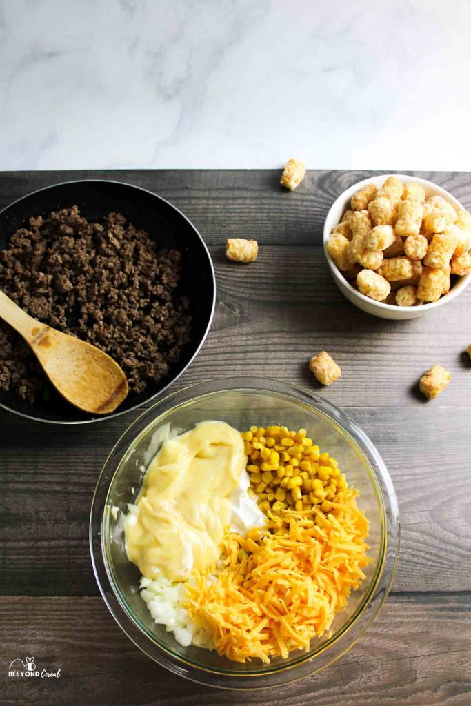 a skillet full of ground beef next to a bowl of other filling ingredients and a bowl of tater tots