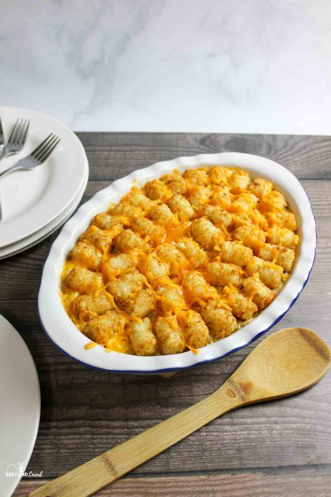 a dish filled with tater tot casserole next to plates and a wooden spoon