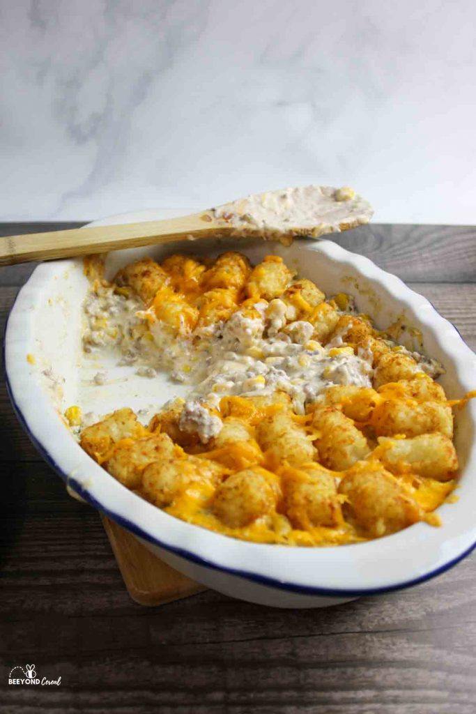 A dish filled with tater tot casserole and missing a few servings with a used spoon resting on top of the dish