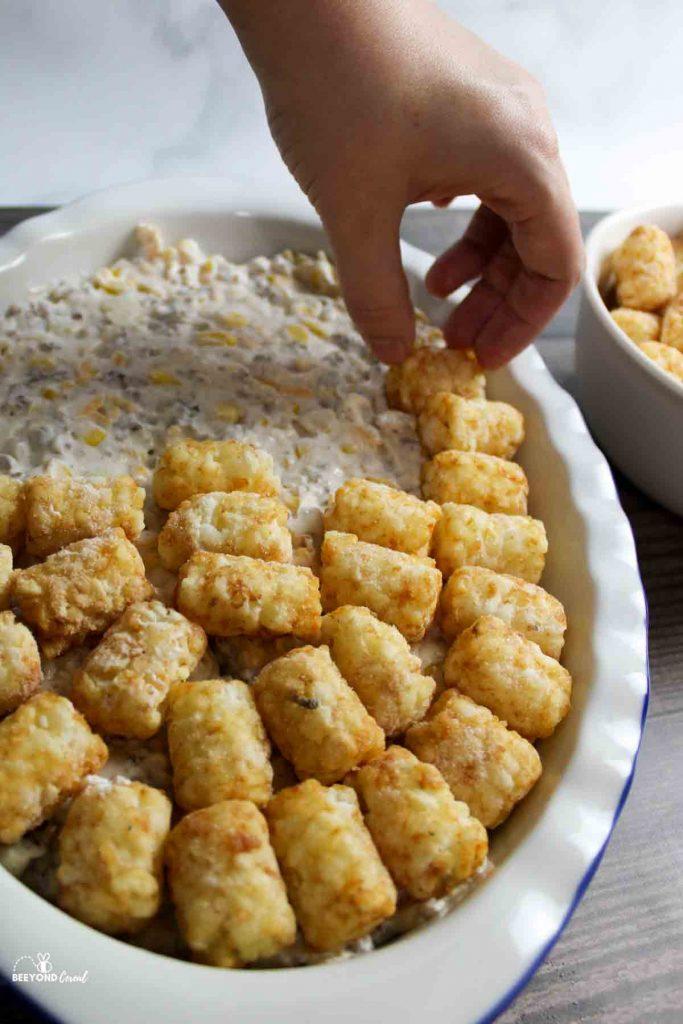 a handputting tater tots on the casserole filling