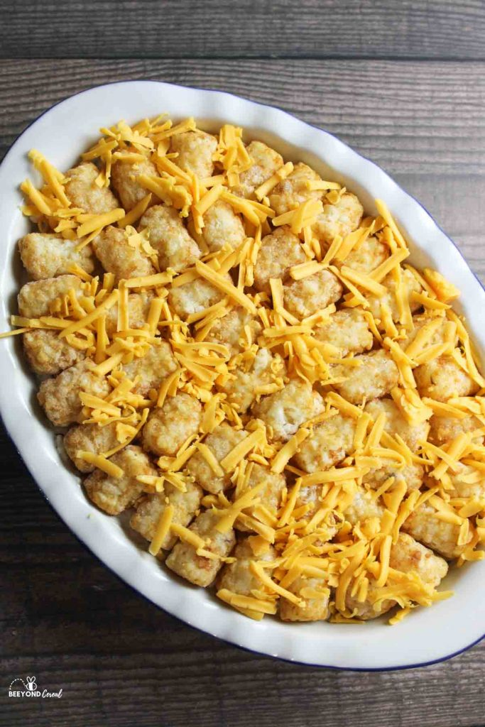 shredded cheese on top of unbaked tater tot casserole