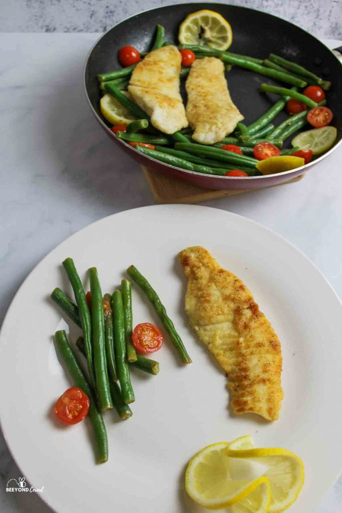 Tilapia, green beans, cherry tomatoes and lemon slices on a plate and in a skillet